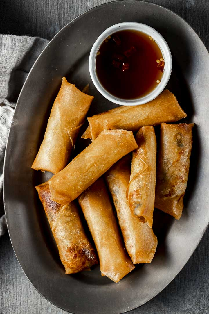 fried spring rolls on a plate with brown dipping sauce on the side