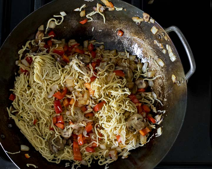 noodles cooking in a wok with diced veggies