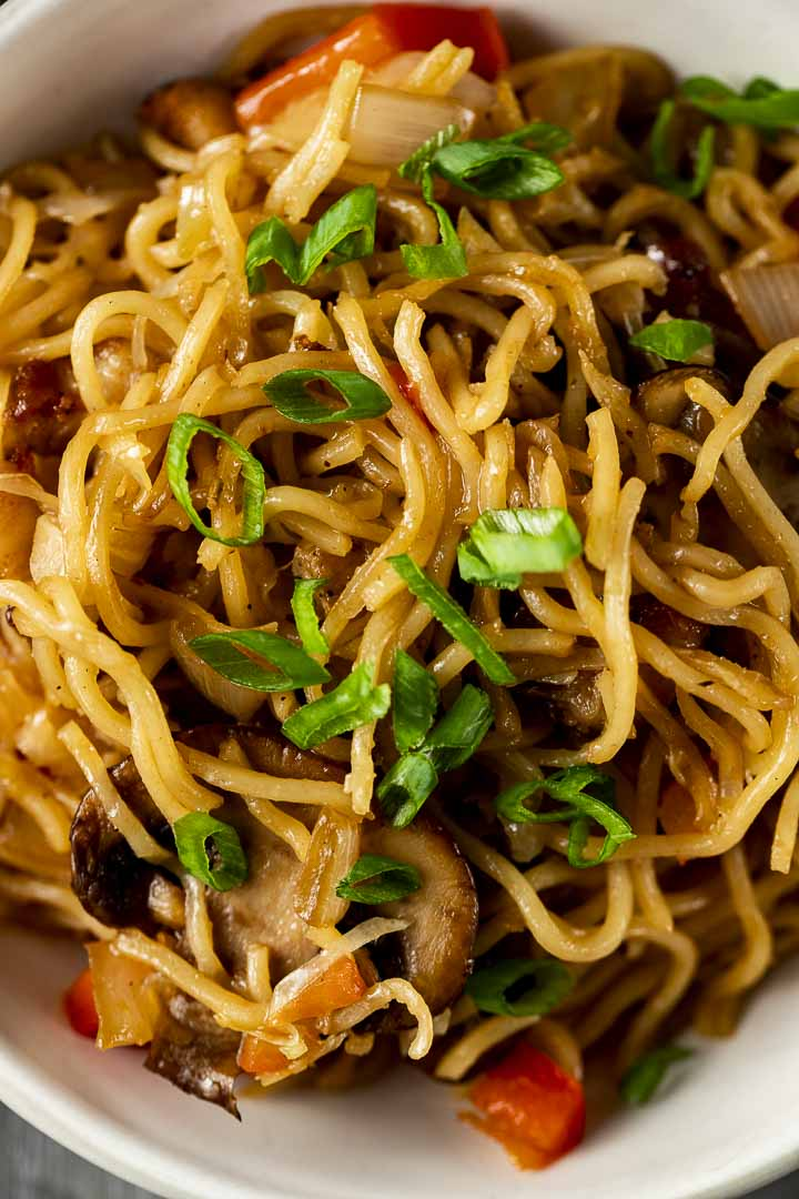 yellow noodles topped with sliced green onions