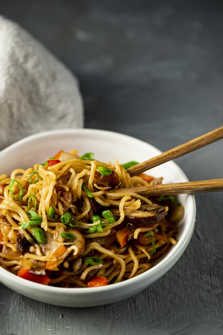 bowl of noodles with vegetables and chopsticks