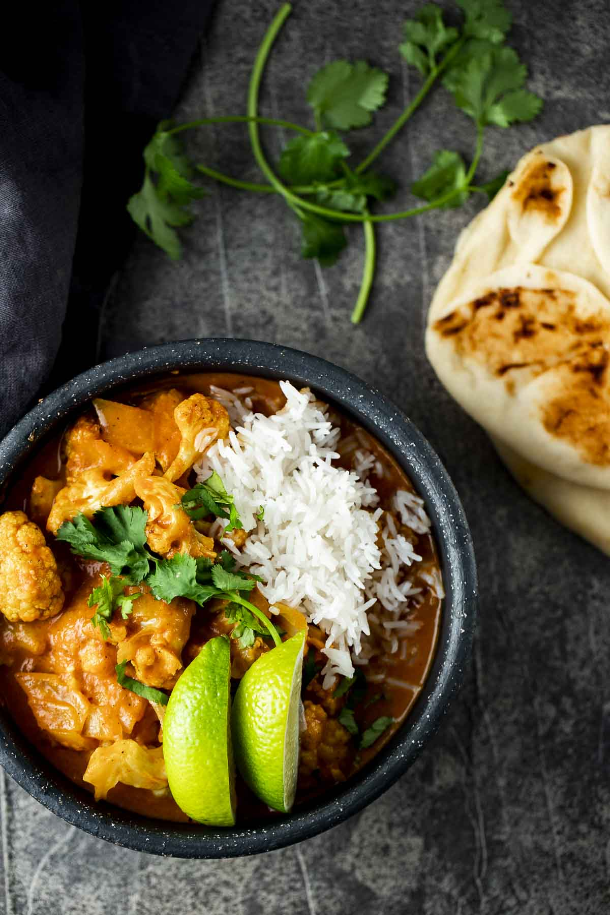a bowl of orange cauliflower curry with white rice and lime slices and naan on the side