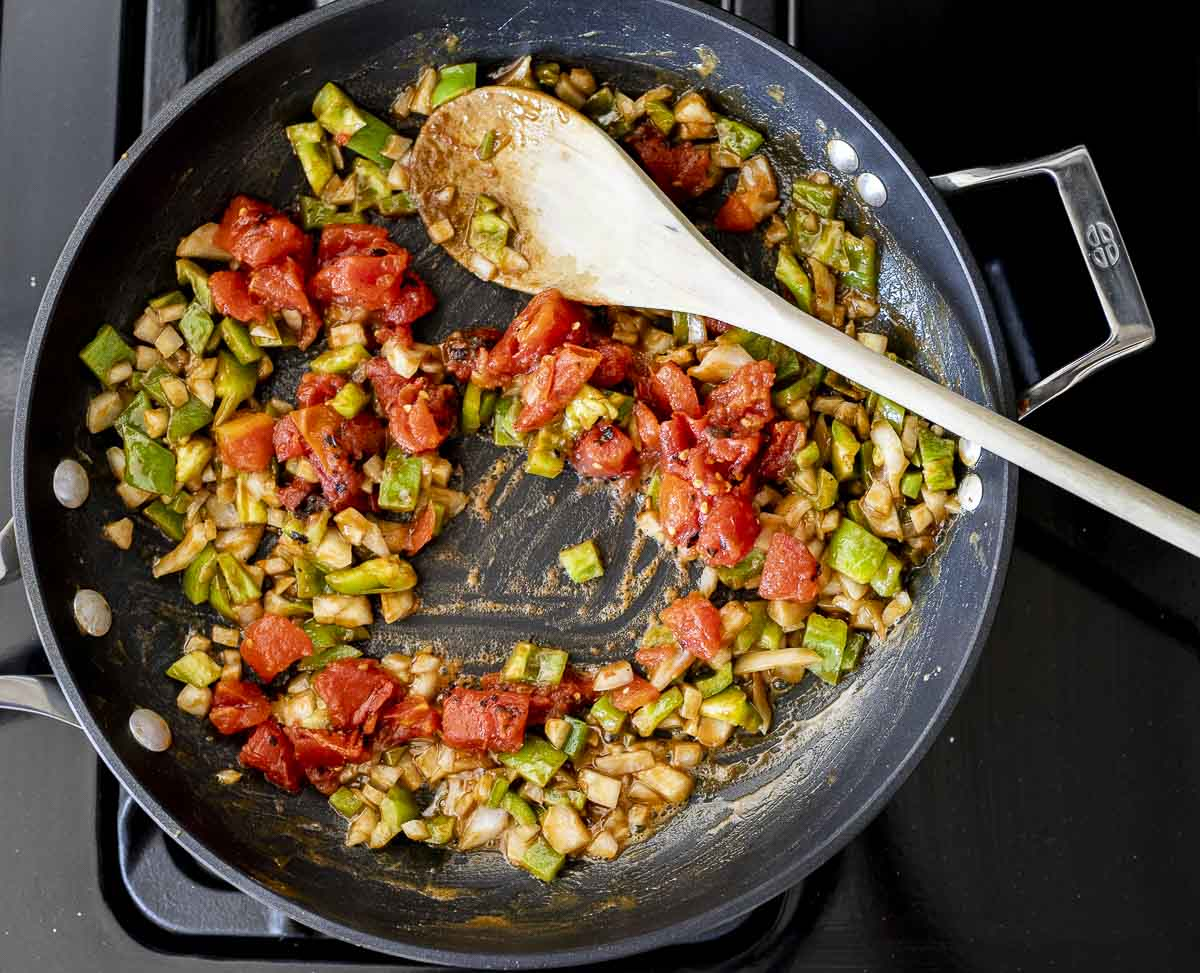 diced onions, tomatoes and green peppers in a skillet