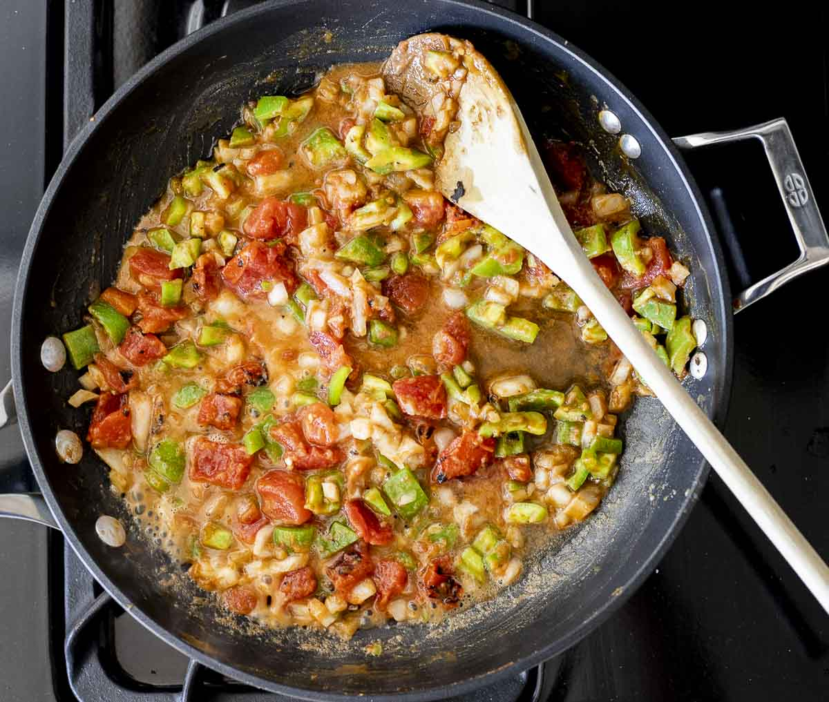 diced tomatoes, onions and green peppers in a skillet with liquid