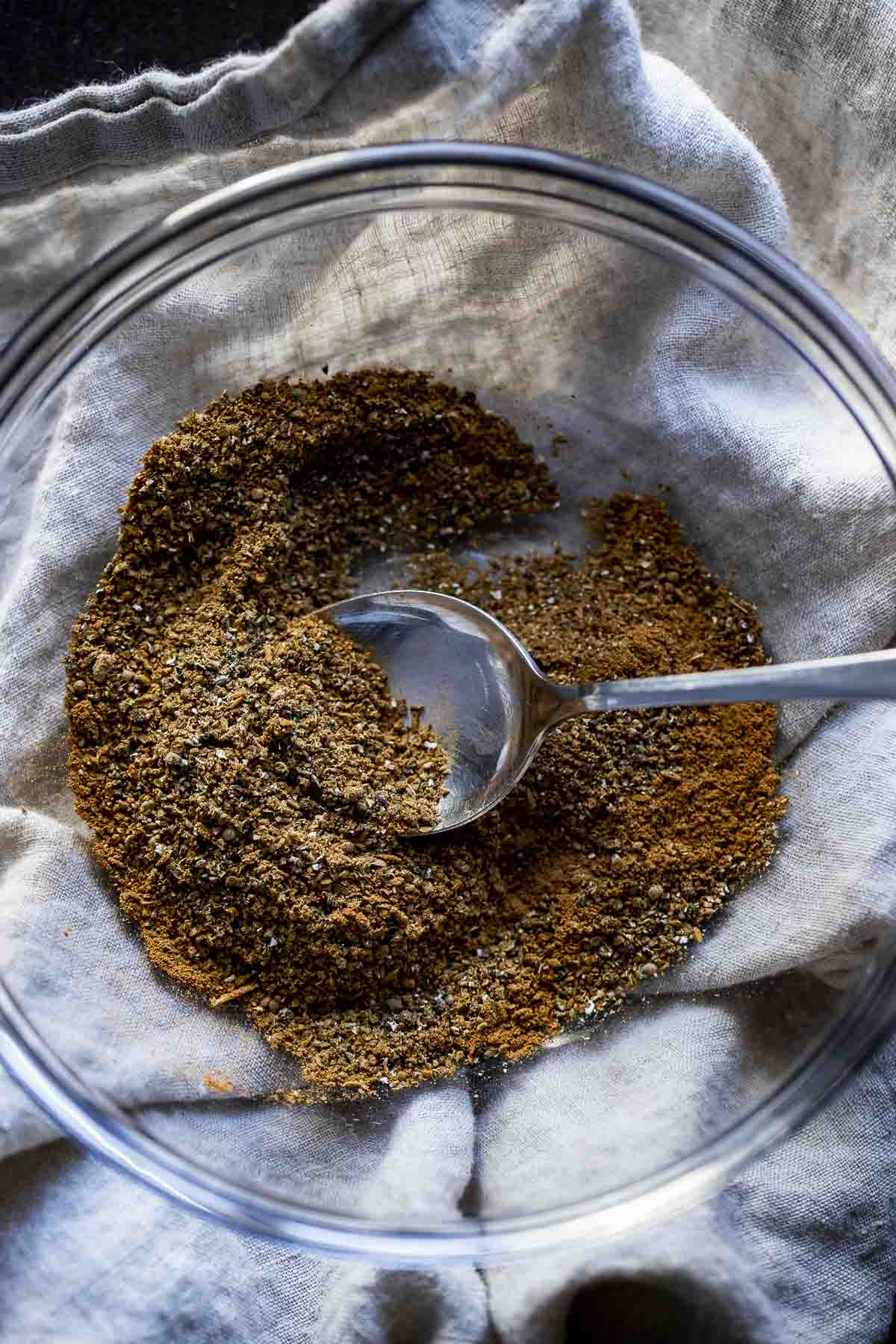 a bowl of brown spices with a spoon