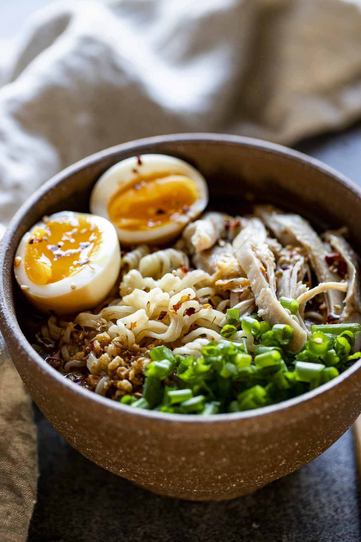 a bowl of noodles soup with an egg cut in half and green onion