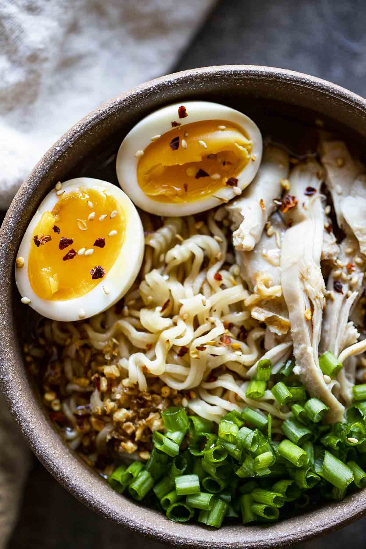 ramen in a bowl with soft boiled eggs, chicken and green onions