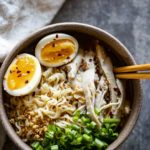 a bowl of ramen with noodles, eggs, chicken and green onions