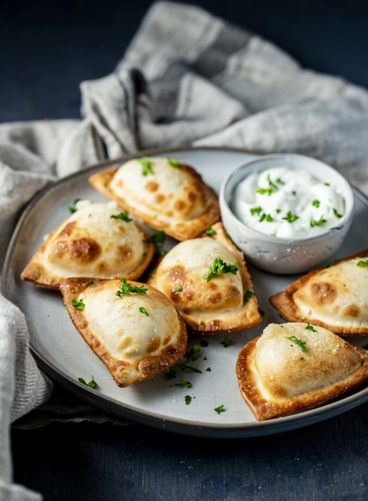 a plate of pierogies garnished with parsley with a cup of sour cream