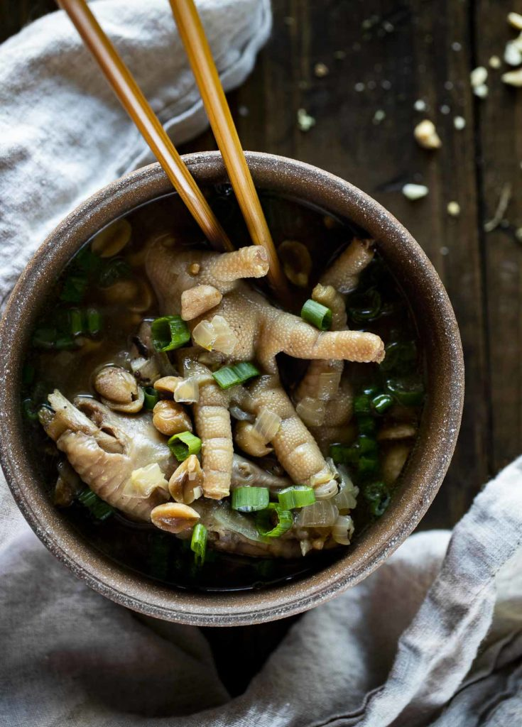 a bowl of chicken feet in broth with chopsticks garnished with green onions