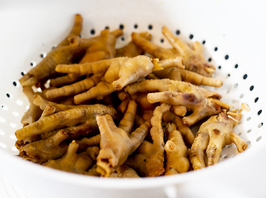 cooked chicken feet in a white strainer