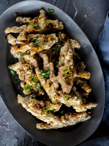 a plate of crispy chicken feet garnished with green onions
