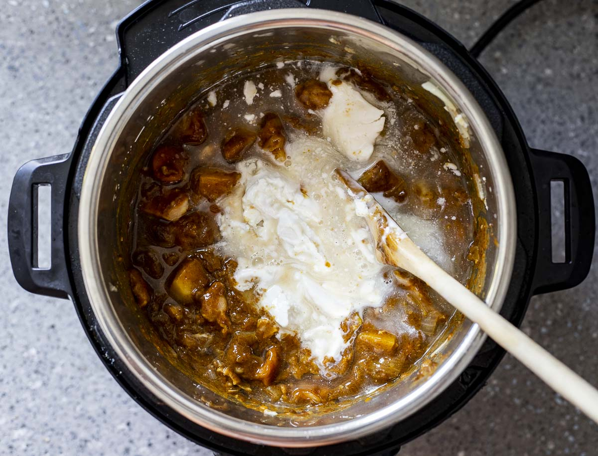 curry with white liquid being stirred in