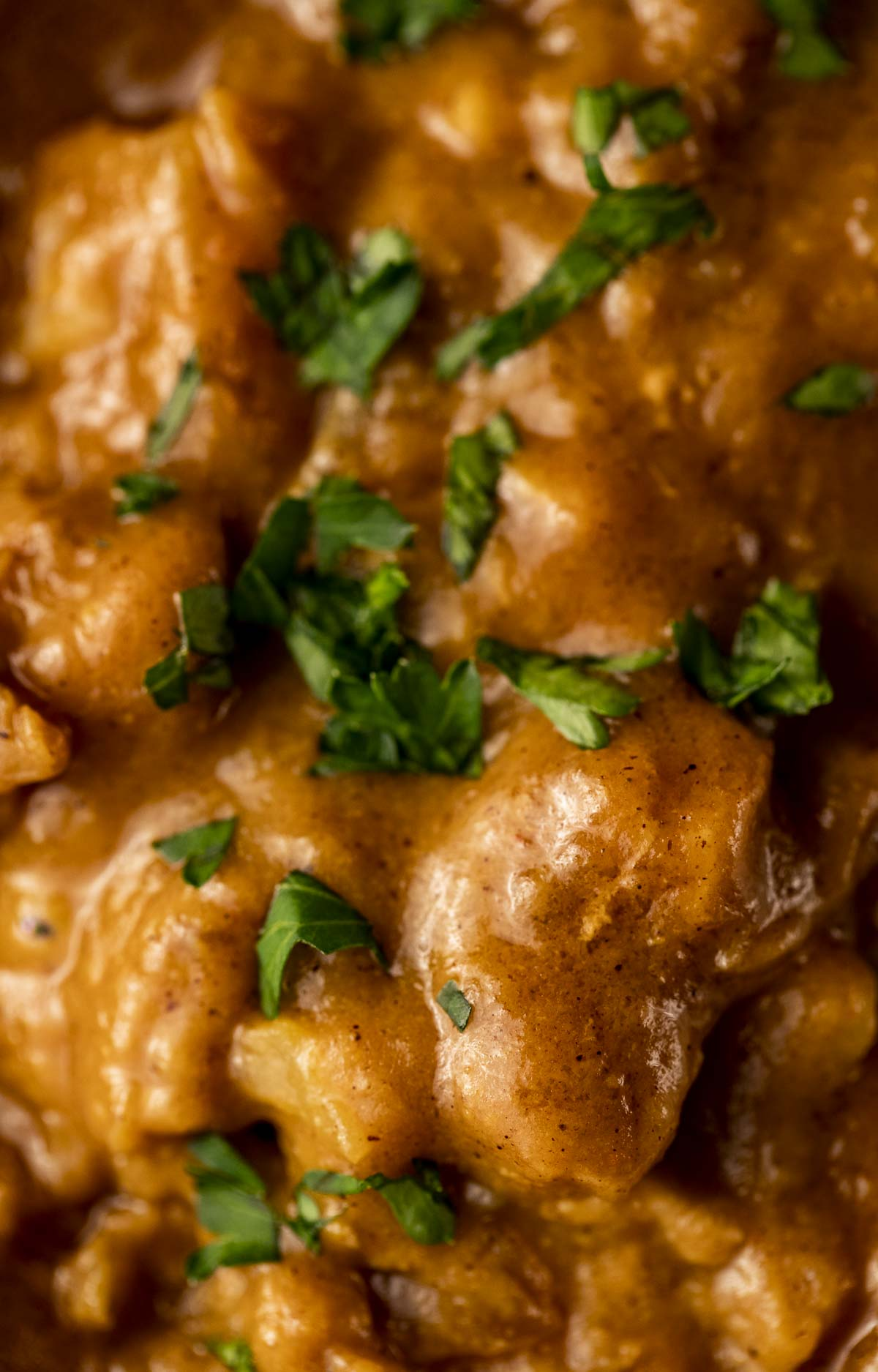 close up photo of chicken and vegetables in an orange sauce