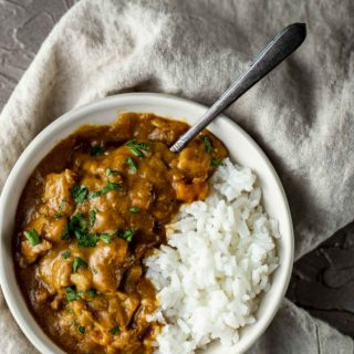 chicken and vegetables in orange curry sauce with rice in a bowl