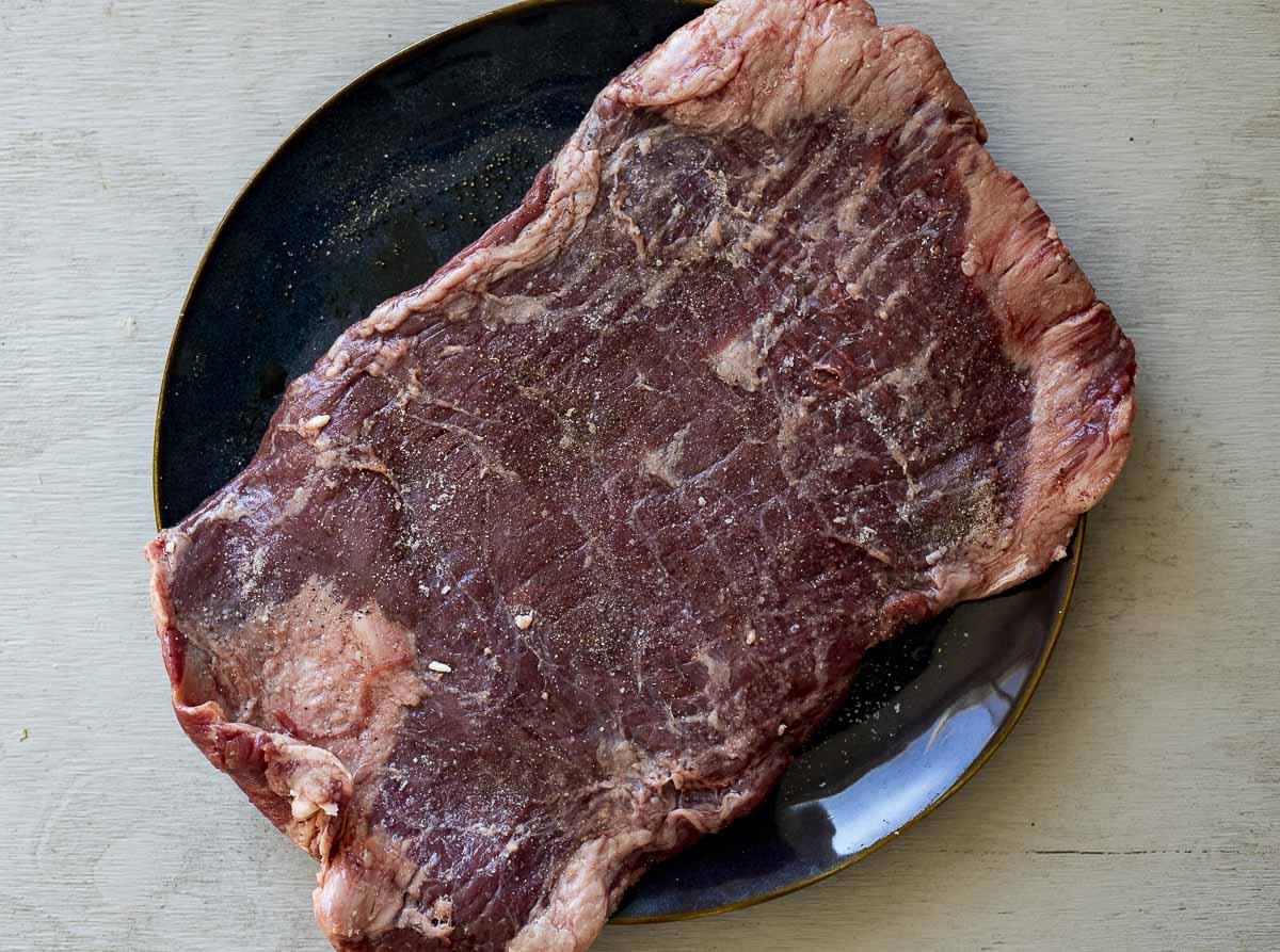 raw flank steak on a plate