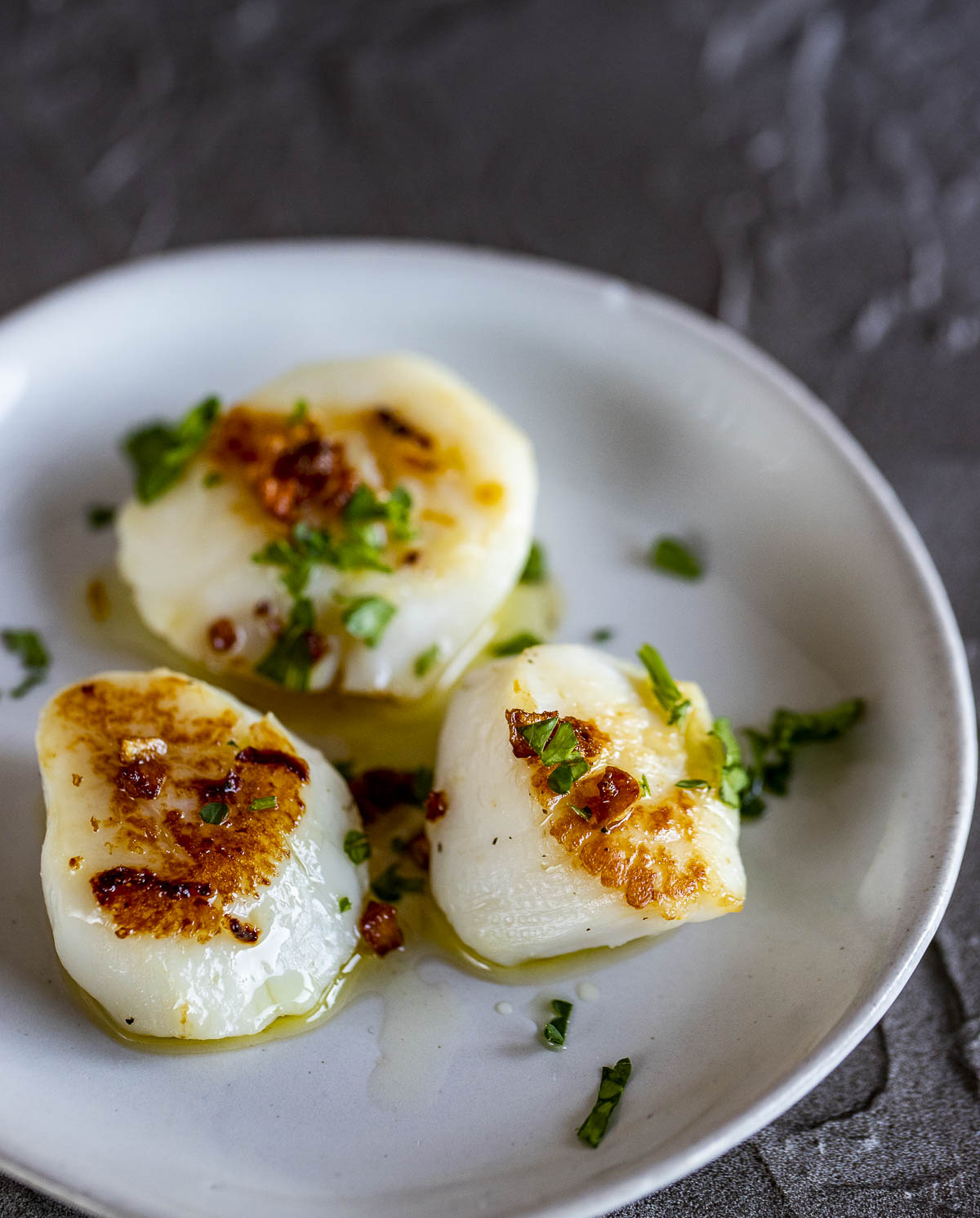 seared sous vide scallops on a plate drizzled in butter and parsley