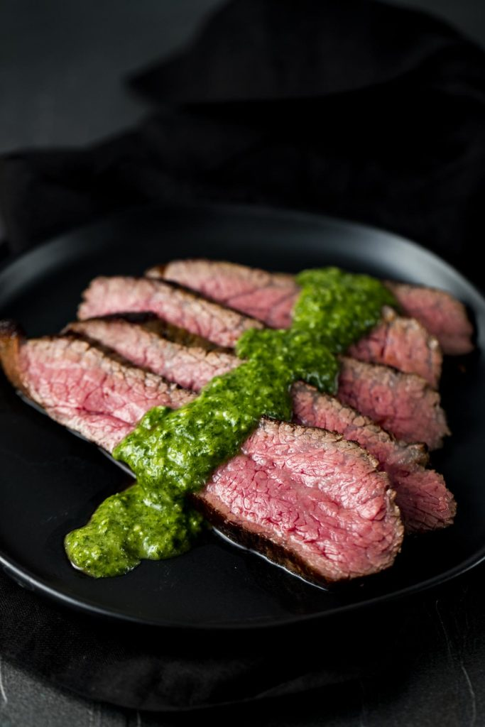 sliced beef on a plate with green sauce
