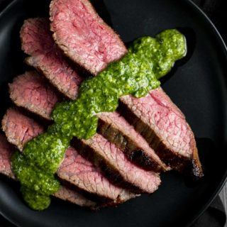 slices of rare beef on a plate with chimichurri sauce