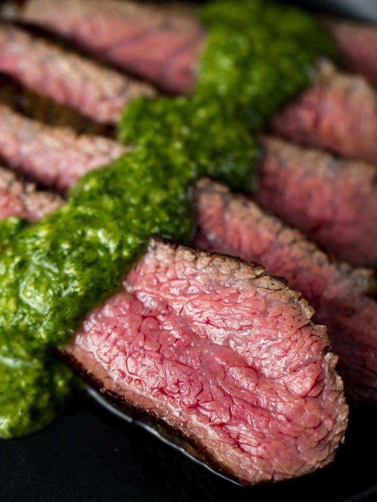 sliced beef with green chimichurri sauce on a plate