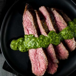 a plate of sliced rare beef drizzled in green sauce