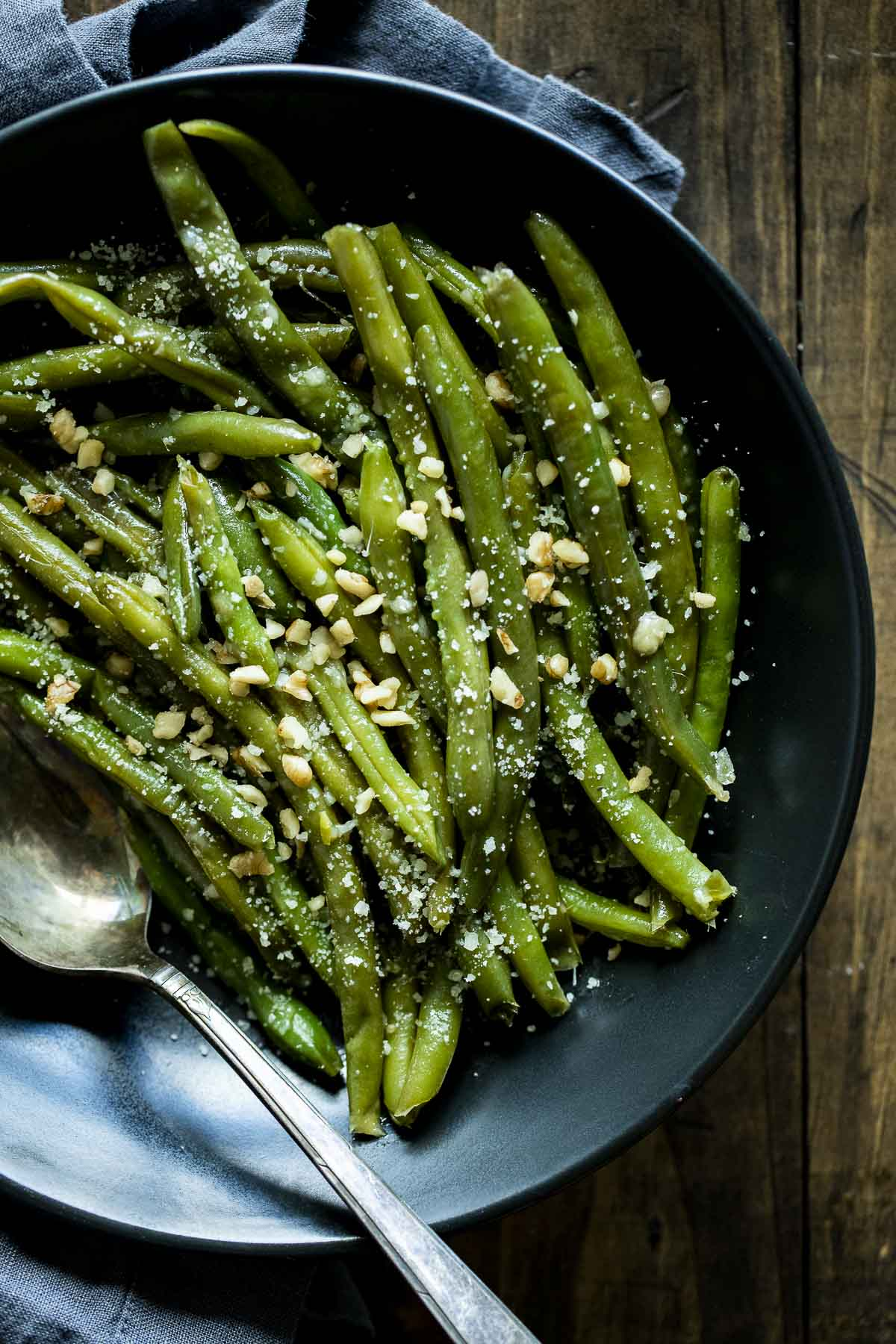Sous vide green beans in a serving bowl with parmesan and walnuts on top.