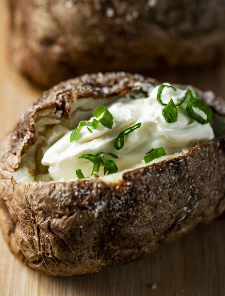 baked potato filled with sour cream and green onions