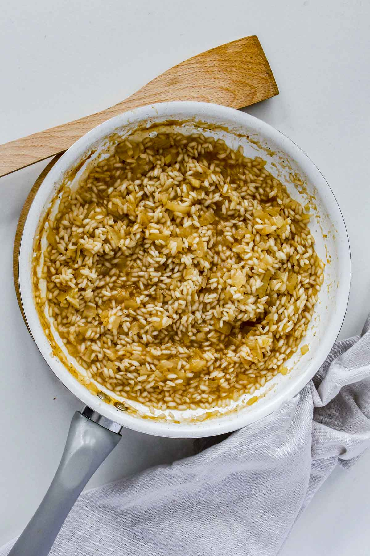 Arborio rice in a pan with the wine reducing.
