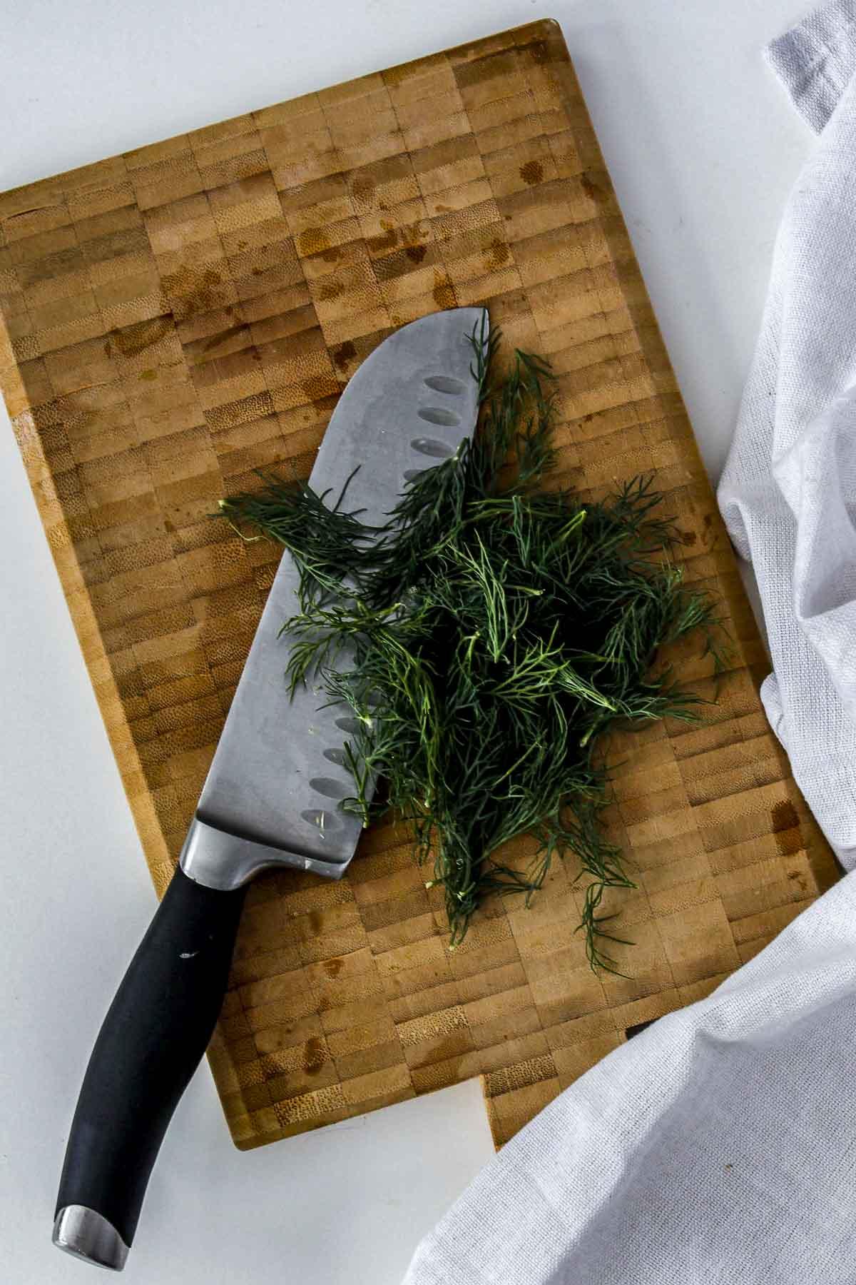 Fresh dill being chopped on a cutting board.