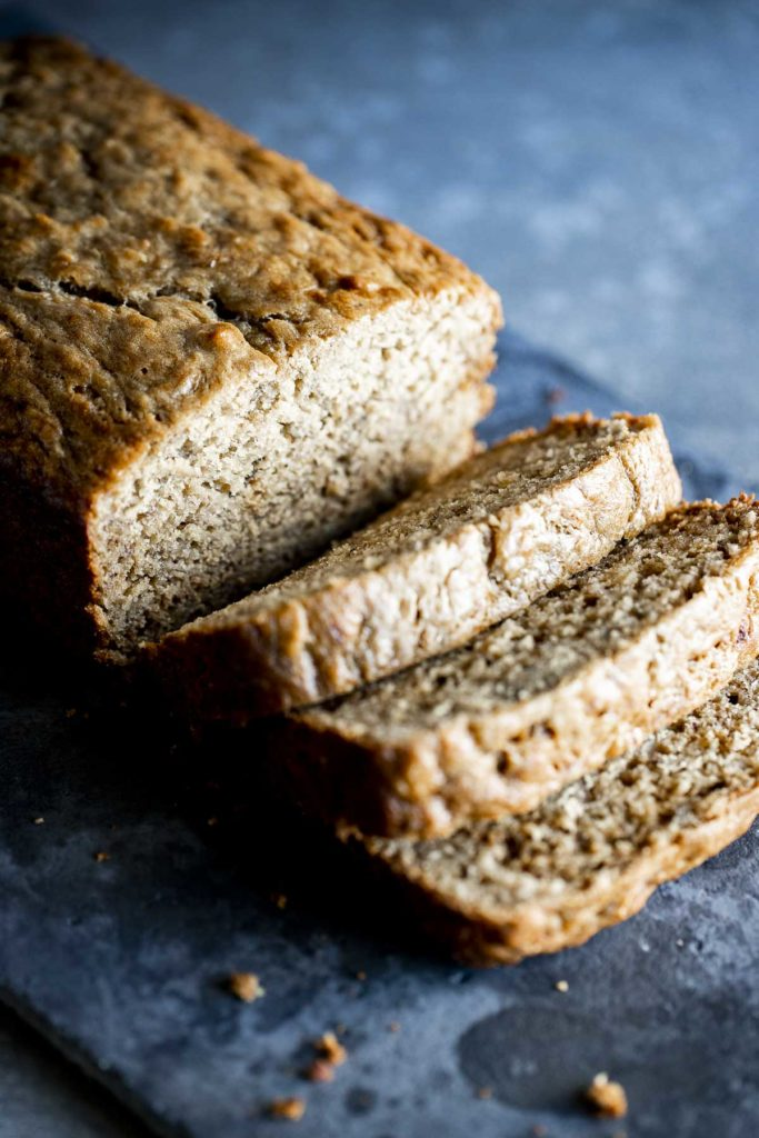 a loaf of brown banana bread being sliced into pieces