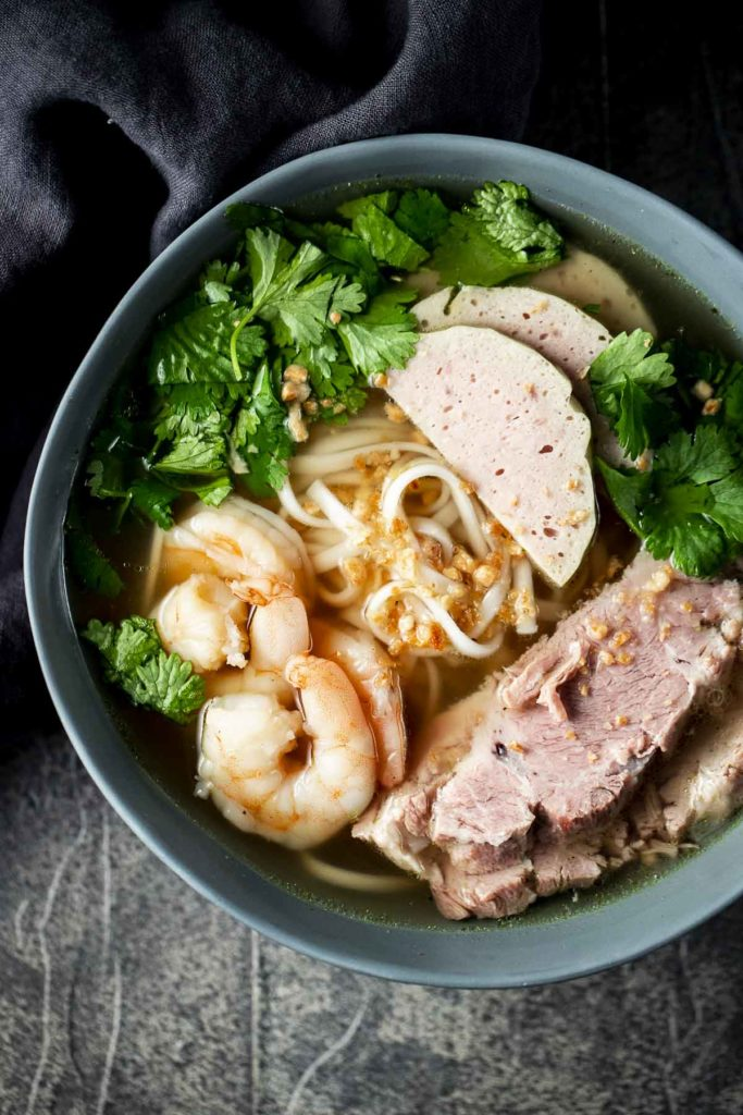 a bowl of noodle soup with sliced meat, shrimp and fresh cilantro