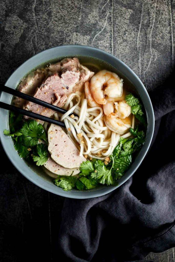 a bowl of noodles soup with chopsticks - sliced pork, shrimp and fresh green herbs
