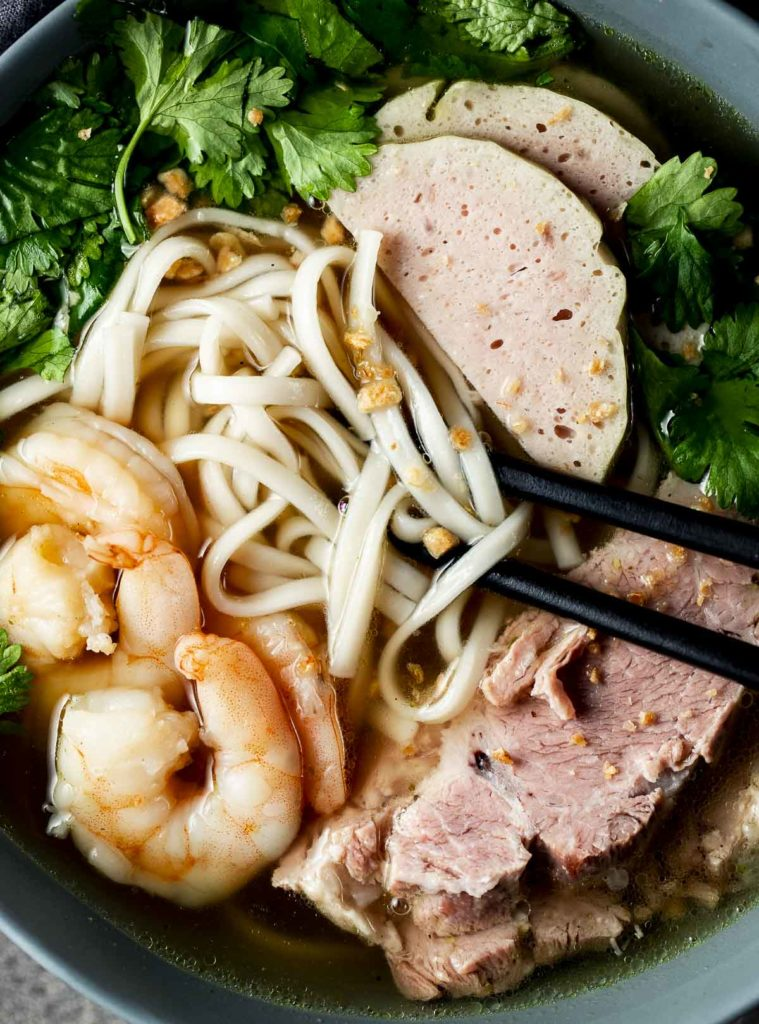 noodles soup in a bowl with chopsticks garnished with fresh herbs, sliced pork and shrimp