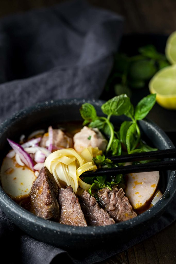 chopsticks in a bowl of noodles soup with sliced beef and fresh mint