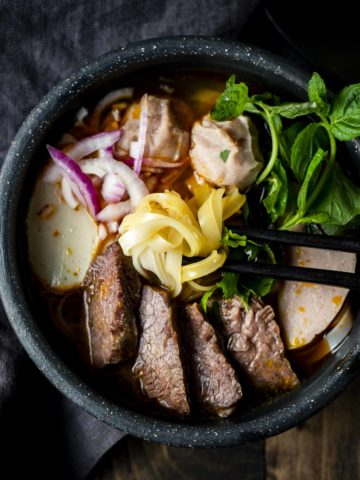 noodles being held by chopsticks in a bowl of beef soup with onions and fresh herbs