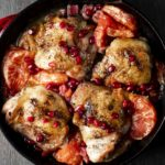 roasted chicken thighs, pomegranate seeds and grapefrut in a red skillet