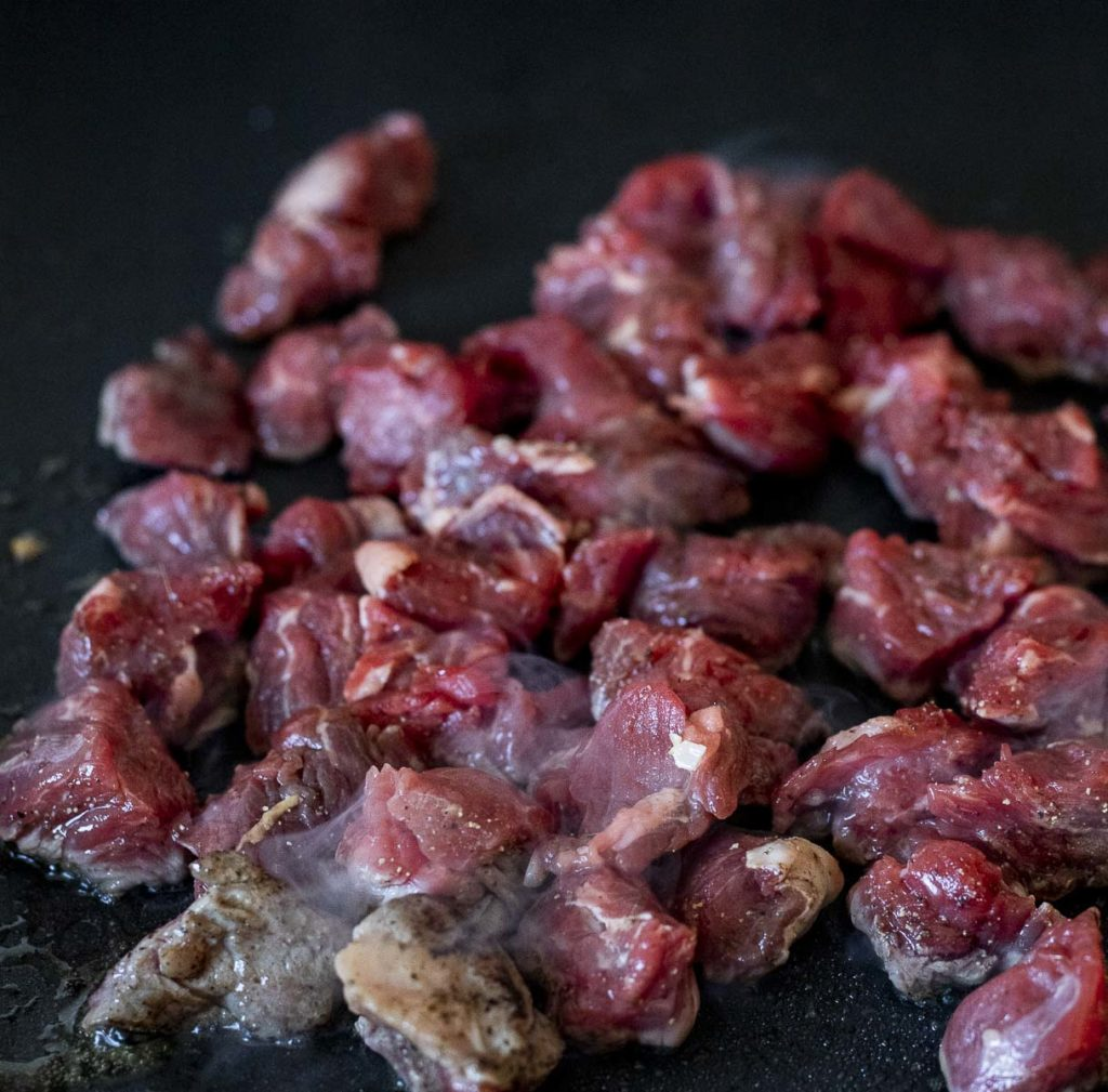 raw beef cubes cooking on a skillet