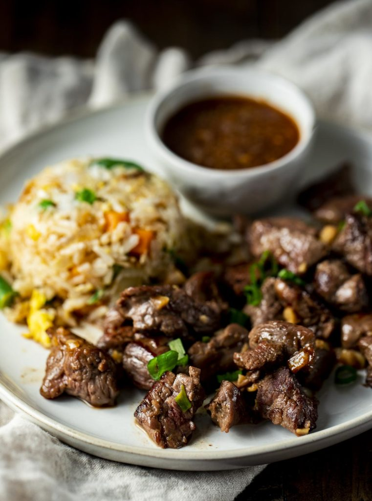 sir fried beef on a plate with rice and a bowl of brown sauce