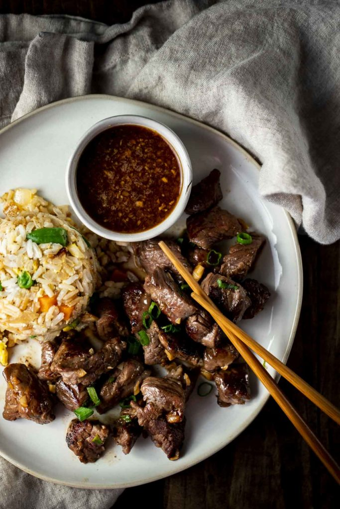 a plate of beef pieces with fried rice and brown sauce on the side