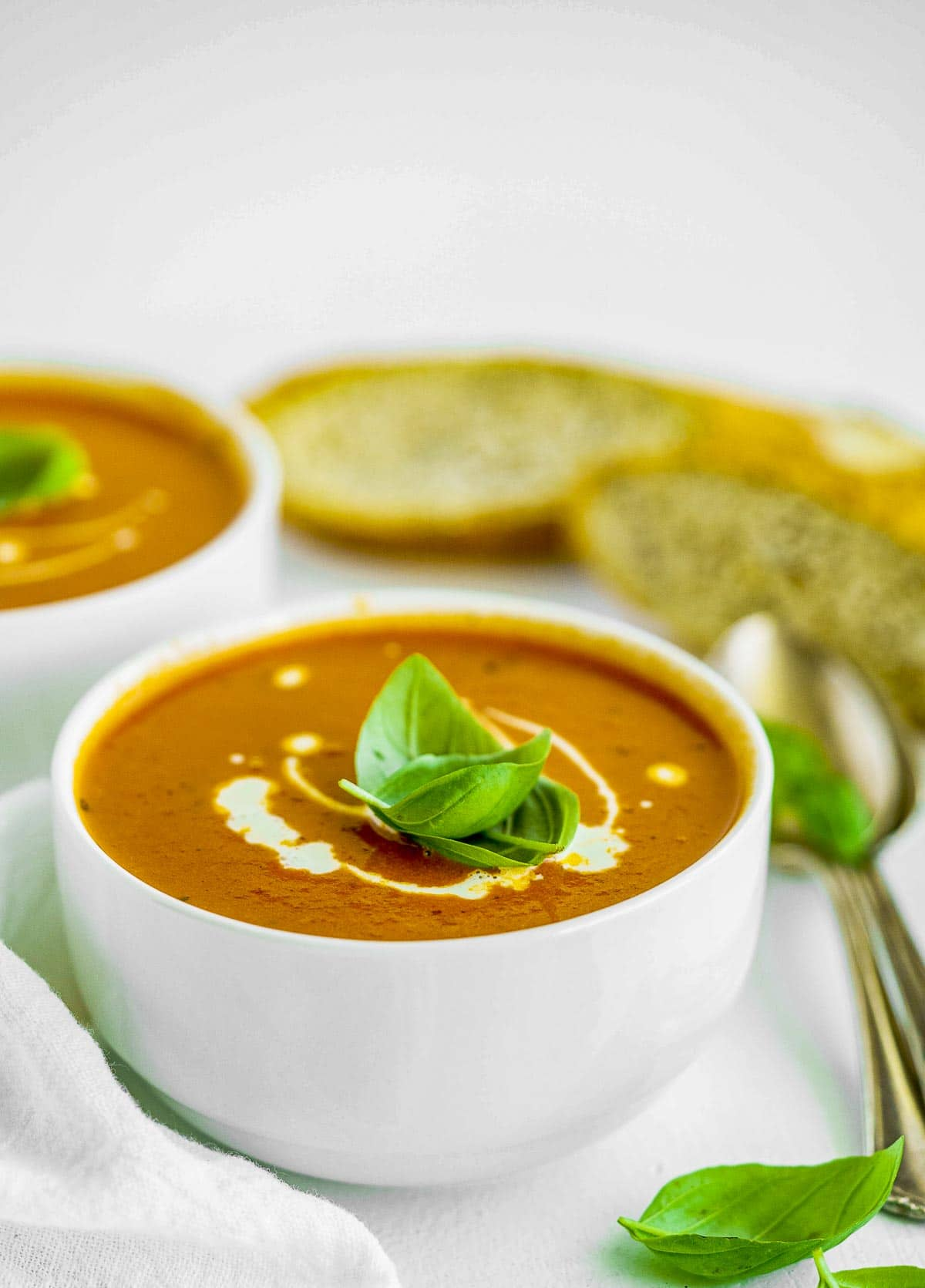 Close up of a bowl of creamy tomato soup with cream and basil.