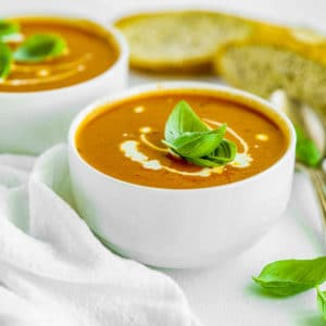 Two bowls of tomato soup with cream and basil as garnish.
