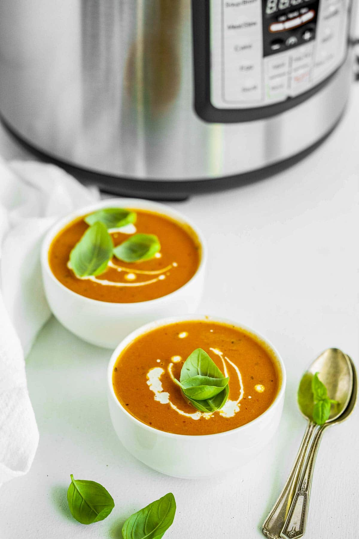 Two bowls of tomato soup beside an Instant Pot.