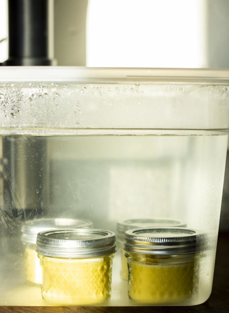 mason jars filled with yellow custard in a large water filled plastic container