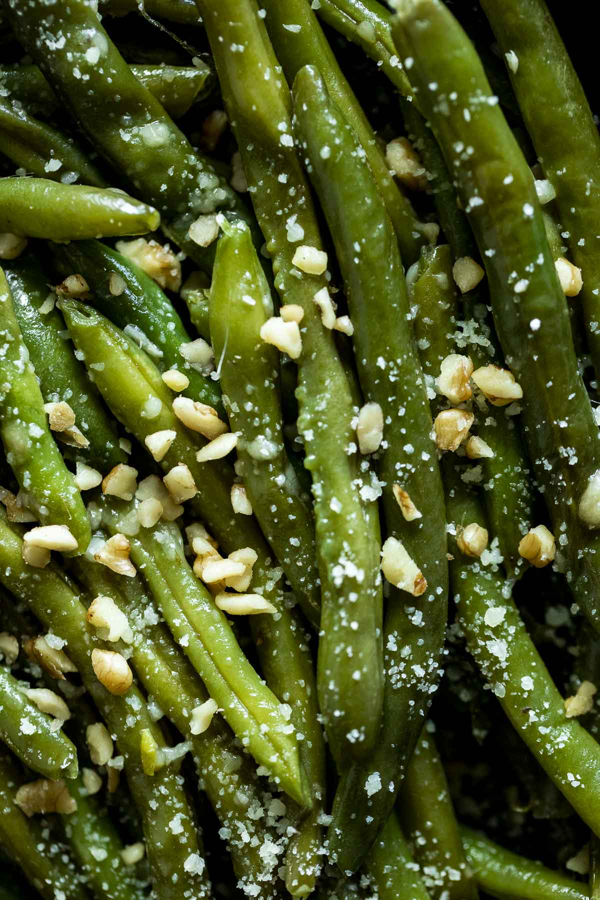 Up close view of green beans topped with walnuts and parmesan cheese.
