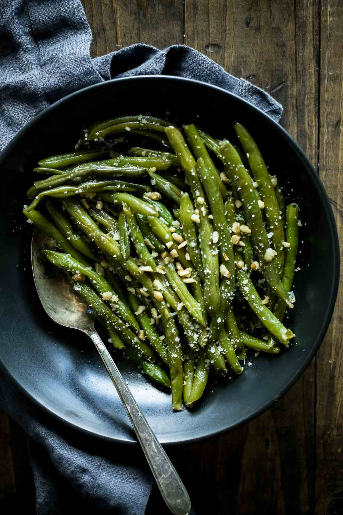 Sous vide green beans in a dark bowl with a spoon.