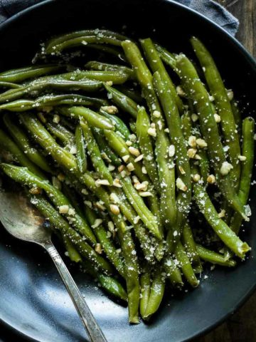 Sous vide green beans in a serving bowl with a spoon and walnuts and parmesan cheese on top.