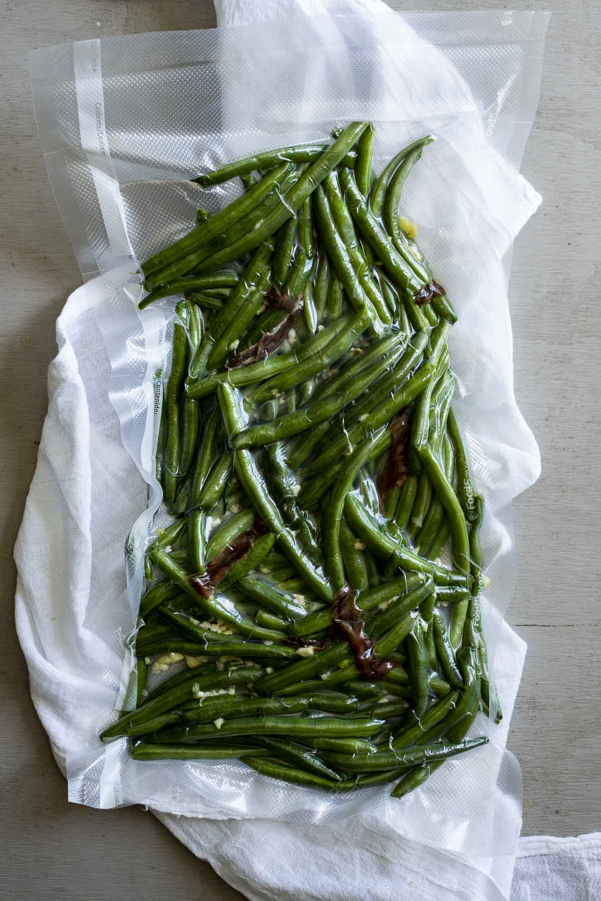 Green beans, garlic, anchovies and oil sealed in a vacuum sealable bag.
