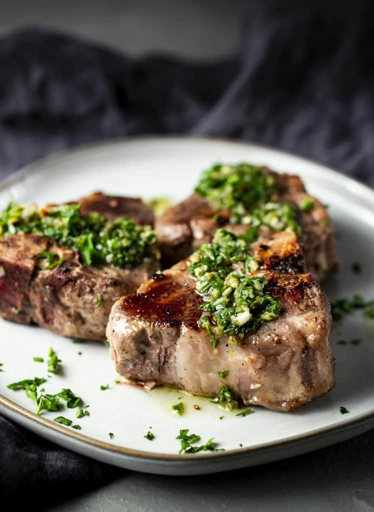 3 lamb chops on a plate drizzled in green herb sauce