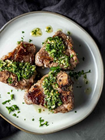 green chimichurri sauce drizzled over lamb chops on a plate