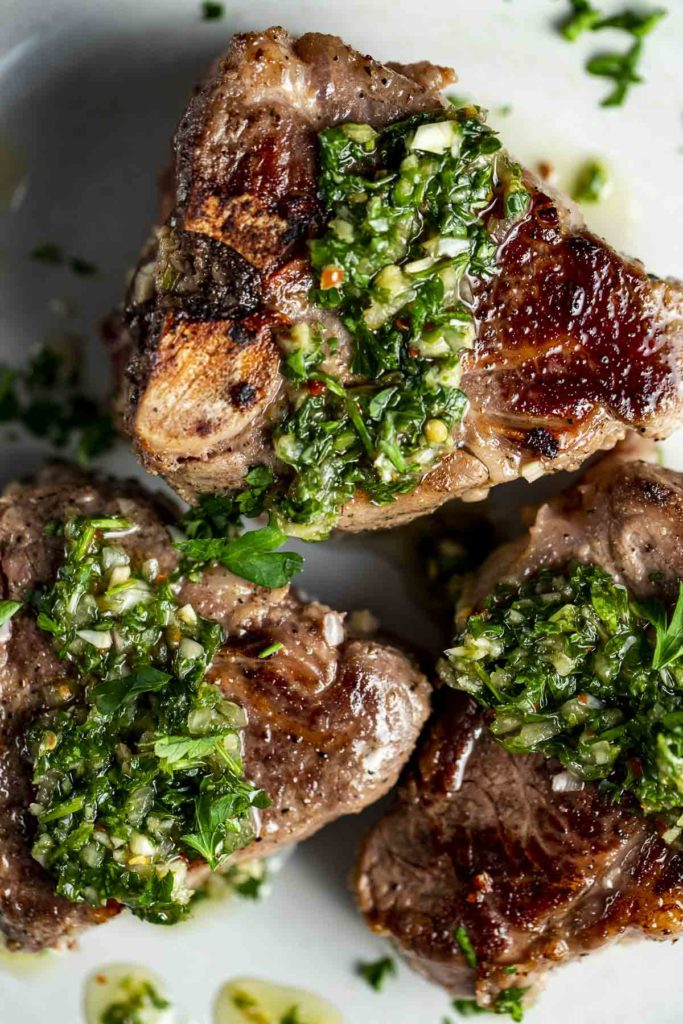 cooked lamb chops with a green sauce over the top