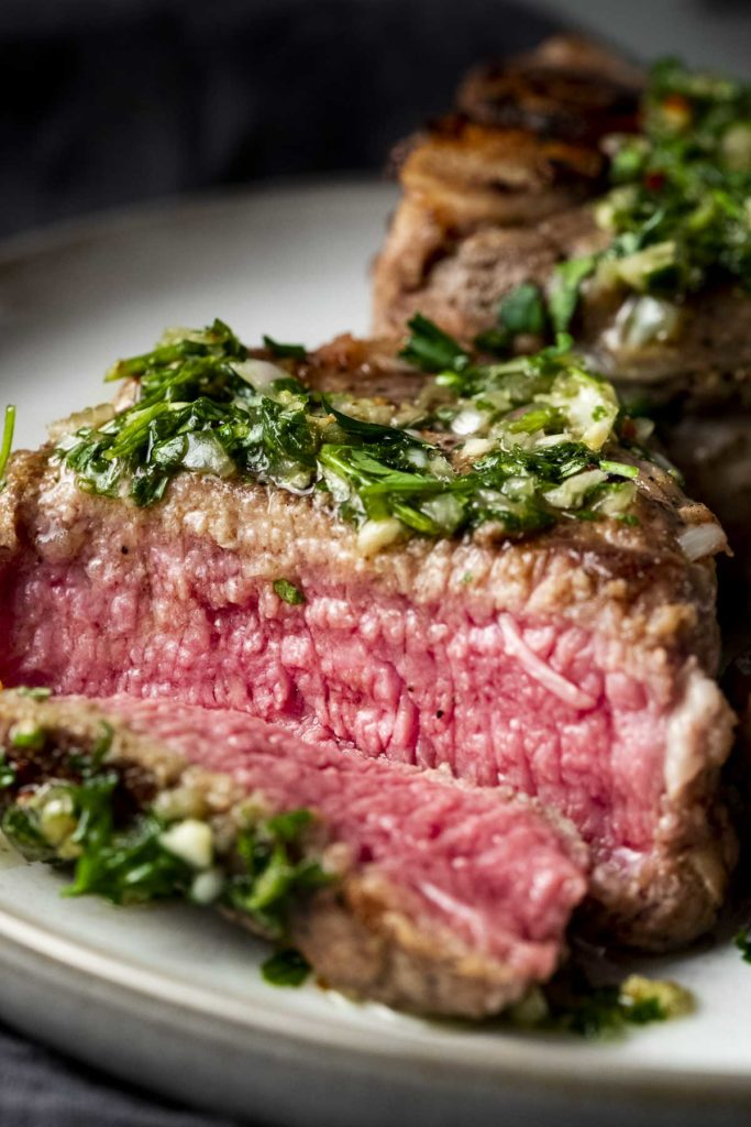 lamb chop cut open to reveal pink inside with green sauce over top